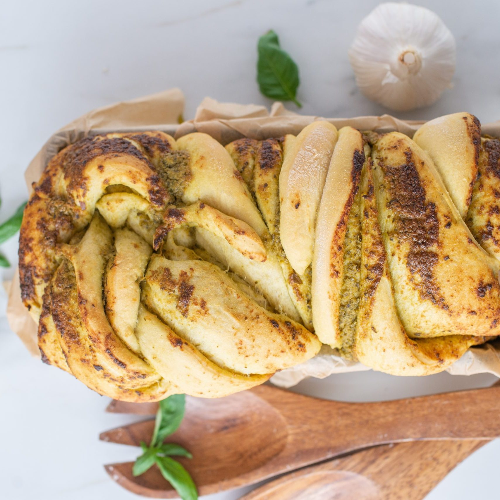 home made braided basil pesto bread on a table